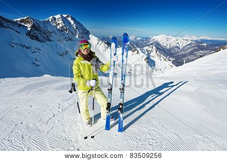Woman in mask standing and holding ski alone