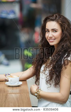 Woman drinking coffee in a cafe supermarket.