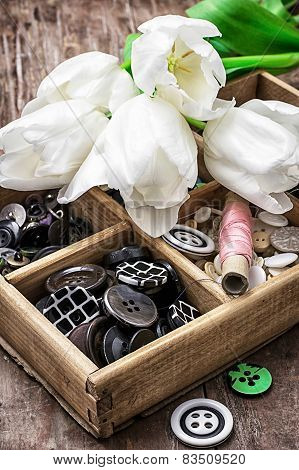Sewing Buttons Against Background Of Bouquet Of White Tulips