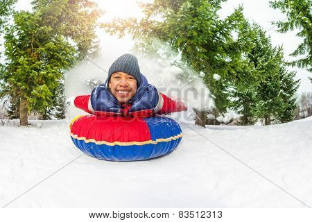 East Asian boy on snow tube in winter alone