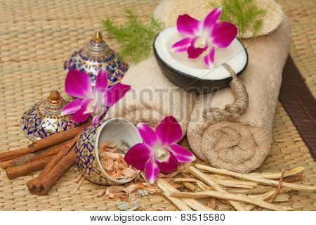 Thai Spa Massage Setting With Spa  Essential Oil , Towel, Herb ,natural Luffa Sponge And With Orchid