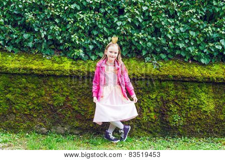 Outdoor portrait of a cute little girl wearing a crown, princess dress