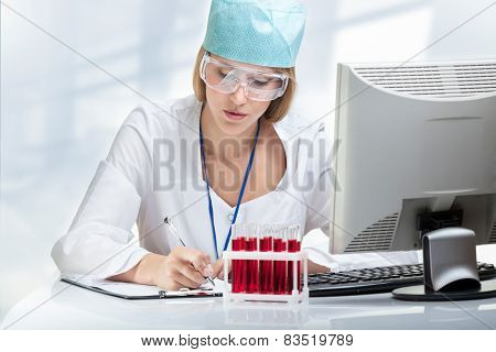 Young Woman Scientist Examining A Test Tube With Red Liquid