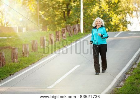 Senior Woman Jogging At The Pedestrian Walkway