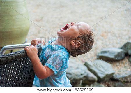 Toddler boy playing under the rain