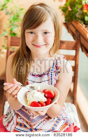 Little girl eating ice cream with strawberry on the balcony