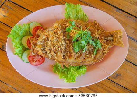 Fried Red Tilapia Fish With Crispy Garlic On The Wood Table