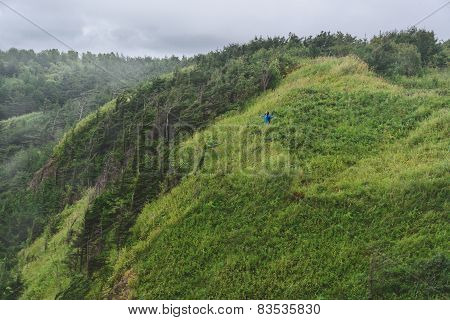 Hiker Standing With Raised Arms On Green Hill