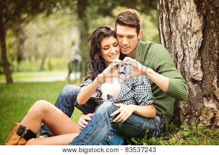 Couple Sitting On The Grass In The Park