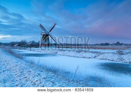 Winter Sunrise Over Windmill In Snow
