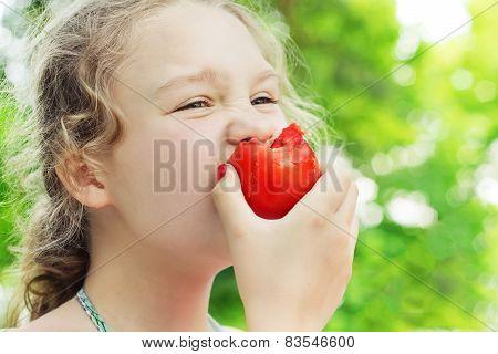 Little Girl Is Eating Ripe Tomato