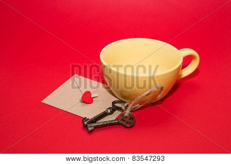 Envelope With Heart, Two Keys And Yellow Cup On A Red Background.
