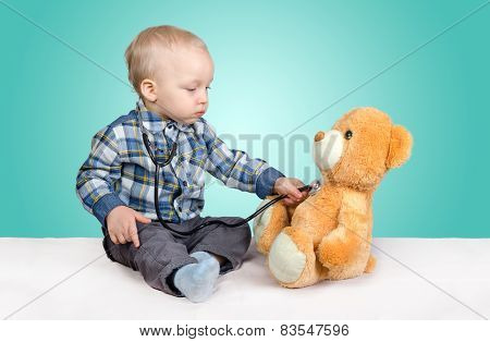 Child Is A Doctor. Playing With Teddy Bear