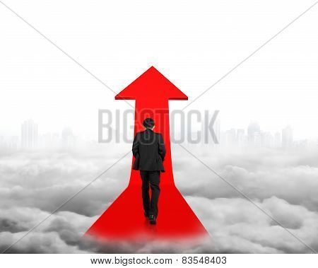 Businessman Walking On Red Arrow Sign Path With Cityscape Cloudscape