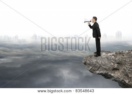 Businessman Using Megaphone Yelling On Cliff With Gray Cloudy Cityscape