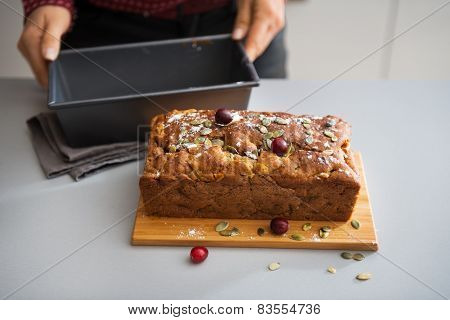 Closeup On Young Housewife Showing Freshly Baked Pumpkin Bread With Seeds