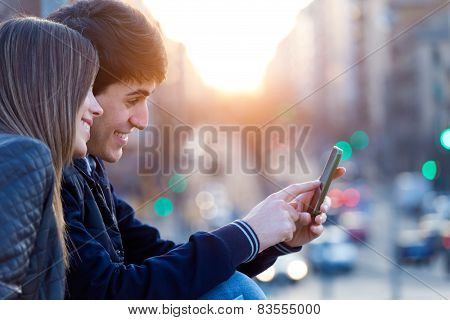 Young Couple Of Tourist In Town Using Mobile Phone.