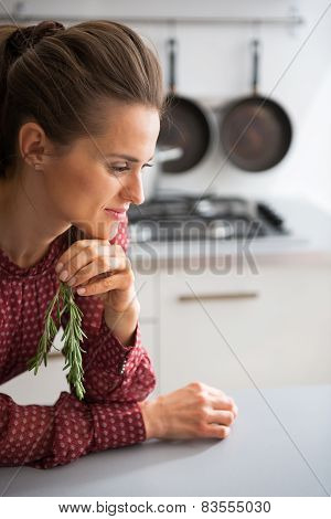 Young Housewife With Fresh Rosmarinus In Kitchen