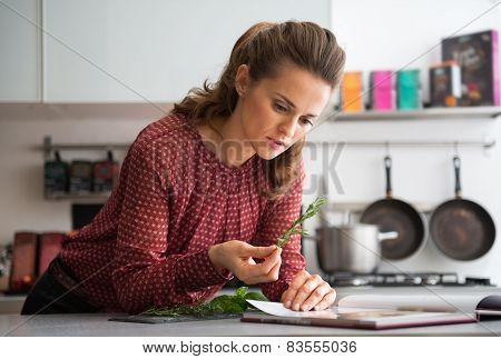 Young Housewife Studying Fresh Spices Herbs In Kitchen