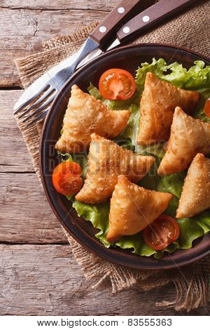 Pastry Samosas On A Plate Close-up. Vertical Top View, Rustic