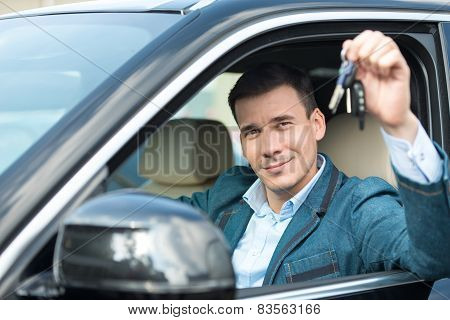 Young man with keys sitting inside car