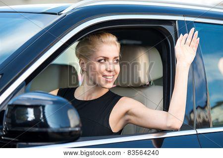 Young woman inside car waving