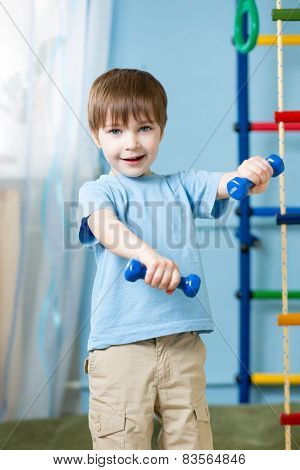 Strong kid exercising with dumbbells