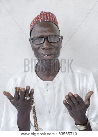 THIAROYE, SENEGAL, AFRICA - JULY 18, 2014 - Unidentified Muslim man praying in front of the Grand Mo