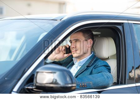 Young man inside car with phone