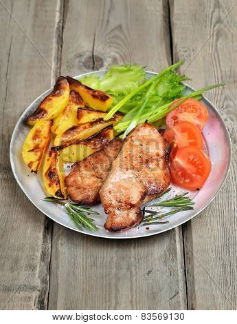 Roasted Pork Chop With Vegetables On Rustic Table