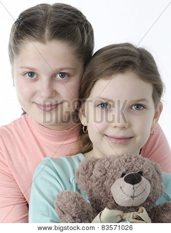 Portrait Of Pretty Little Girls Holding Teddy Bear On White