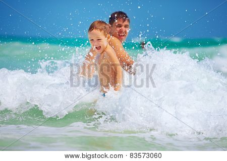 Happy Father And Son Having Fun In Waves, Summer Vacation