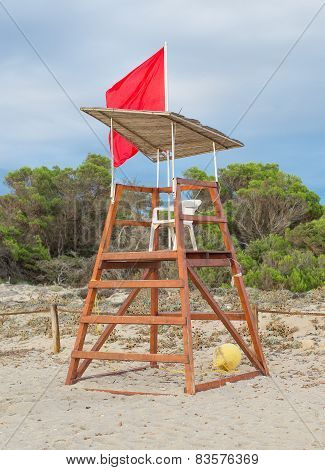 Empty Lifeguard Tower With Red Flag On The Beach.