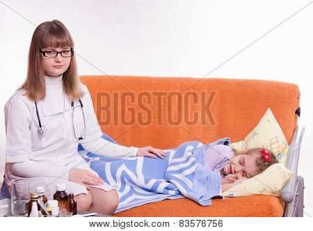 Pediatrician Sitting At The Bedside Of A Sick Child
