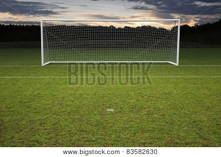 Empty Amateur Football Goal Posts And Nets Shot At Sunset