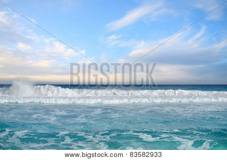 White Foamy Waves And Gradually Darkening Color Of Sea Water With Stripe Of White Sandy Beach