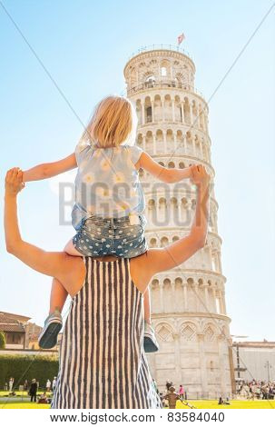Baby Girl Sitting On Mothers Shoulders And Looking On Leaning Tower Of Pisa, Tuscany, Italy. Rear Vi
