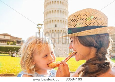 Happy Mother And Baby Girl Eating Pizza In Front Of Leaning Towe