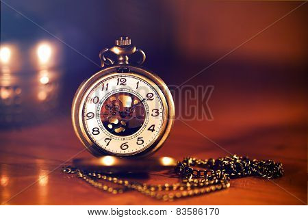 Retro Gold Pocket Watch In Beautiful  Candle Light On Brown Background.