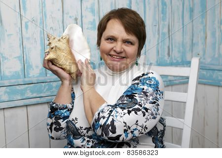 Old woman holding a seashell. Selective focus on her face. Blue marine background.