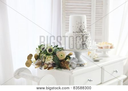 White Wedding Cake With Silver Decoration And Wedding Bouquet