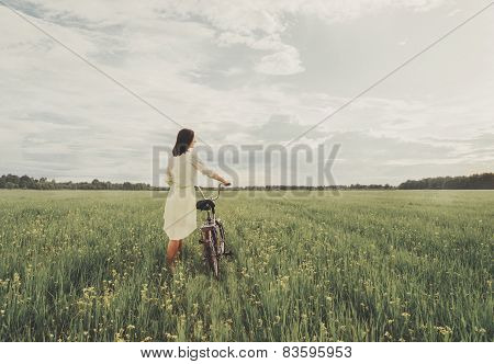 Woman Walking With A Bicycle On Summer Meadow