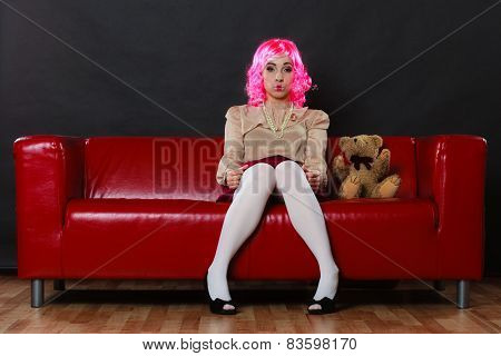 Young childlike woman wearing like puppet doll sitting with teddy bear toy on red couch