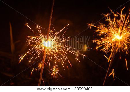 Burning Sparklers On A Dark Evening From Close