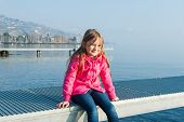 stock photo of pier a lake  - Portrait of a sweet little caucasian girl sitting on a pier on Lake Geneva with the Lavaux in a misty background - JPG
