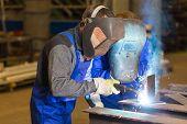 image of welding  - Two steel construction workers welding metal pieces - JPG