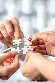 image of interlocking  - Four hands fitting together matching interlocking puzzle pieces conceptual of teamwork and problem solving - JPG