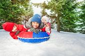 stock photo of snow forest  - Excited girl and two boys on snow tube in winter during day in the fir tree forest - JPG