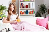 foto of couch potato  - Happy Woman Eating Chips on the couch - JPG
