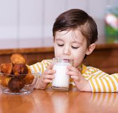 stock photo of tongue  - Cute little boy is dipping his tongue in the glass of milk - JPG